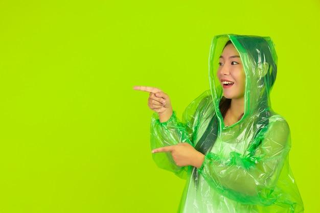 Garota bonita feliz, vestindo roupas verdes, guarda-chuva e casaco, dia chuvoso.