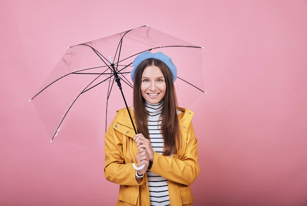 Garota bonita legal na capa de chuva amarela com guarda-chuva