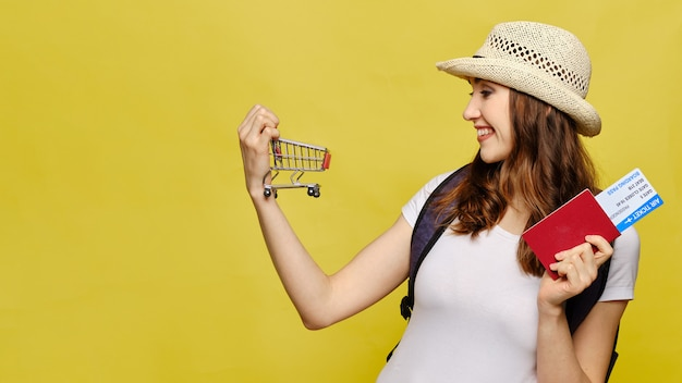 Garota bonita roupas casuais com um passaporte e bilhetes detém um carrinho como um conceito de venda de viagens.