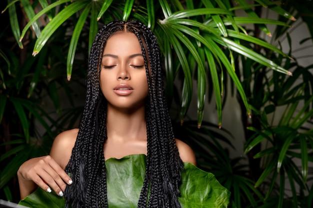 Garota bonita sedutora raça mista com os olhos fechados e dreadlocks posando em folhas verdes. cuidados e cosméticos naturais