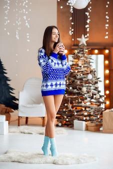 Garota bonita uma camisola quente de férias com uma xícara de chá quente com canela