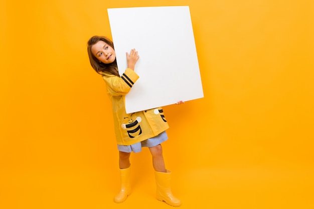 Garota bonita uma capa de chuva segura um cartaz com uma maquete sobre um fundo amarelo