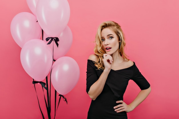 Garota branca interessada em pé na parede rosa perto de um monte de balões de festa. winsome mulher caucasiana em roupa preta, tocando suavemente seu rosto.