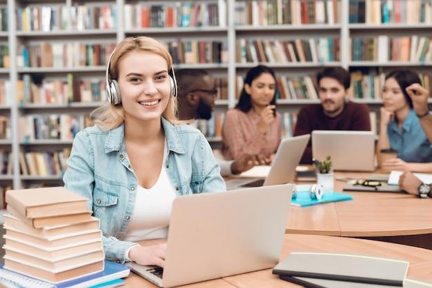 Garota branca trabalhando no laptop com fones de ouvido.