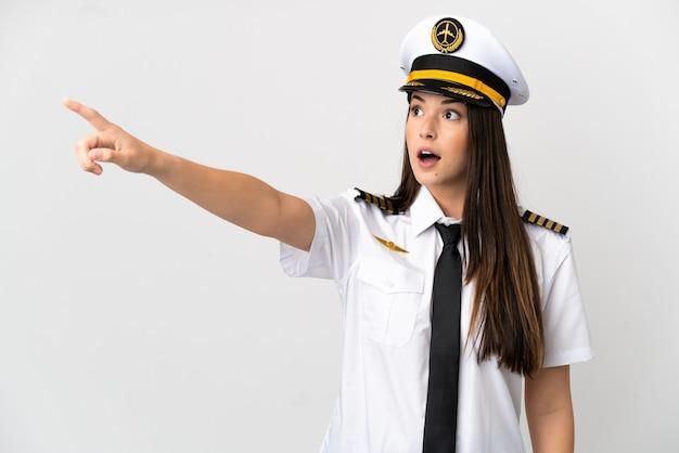 Garota brasileira piloto de avião sobre fundo branco isolado apontando para longe