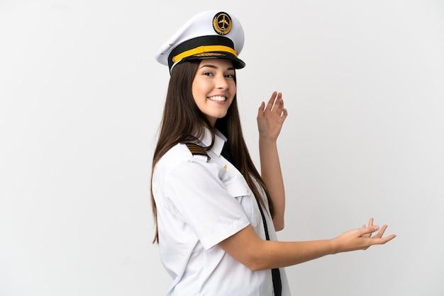 Garota brasileira piloto de avião sobre fundo branco isolado estendendo as mãos para o lado para convidar para vir