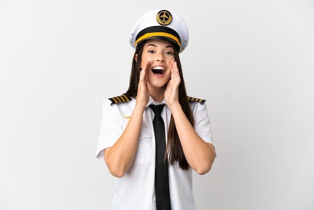 Garota brasileira piloto de avião sobre fundo branco isolado gritando e anunciando algo
