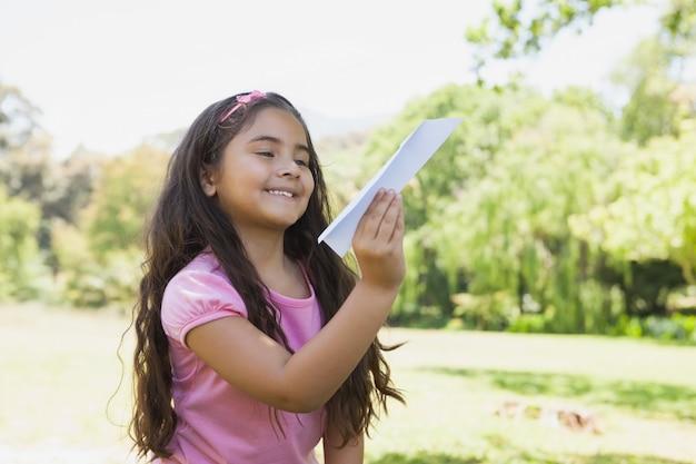 Garota brincando com um avião de papel no parque