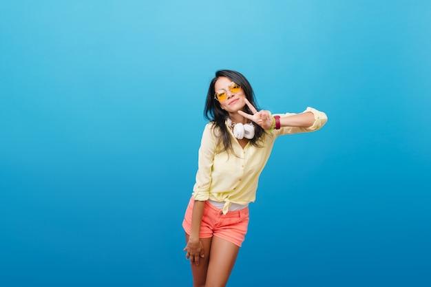 Garota bronzeada desportiva em shorts jeans, posando com prazer. retrato interior da magnífica mulher europeia em roupa de rua usa fones de ouvido grandes.