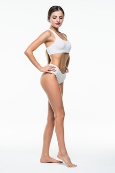 Garota bronzeada magro em lingerie branca posando isolado na parede branca. conceito de cuidados de beleza e corpo