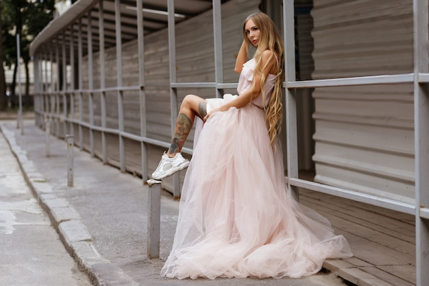 Garota bronzeada no vestido de casamento na cidade do gueto