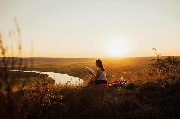 Garota calma lendo um livro na colina com paisagem perfeita, aproveitando o feriado