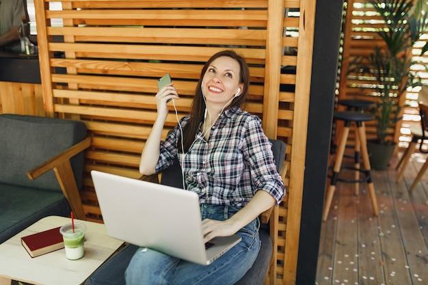 Garota calma na rua ao ar livre verão café café de madeira sentado com um moderno laptop pc, telefone celular