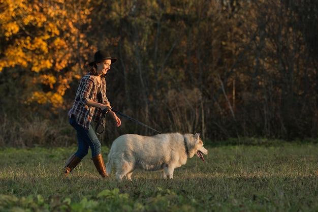 Garota caminha com husky