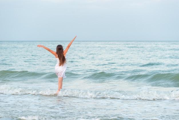 Garota caminhando ao longo das ondas do mar em um verão ensolarado