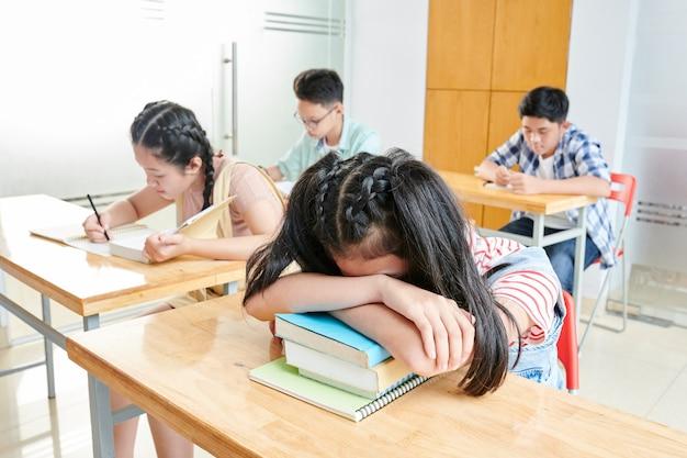 Garota cansada apoiando-se nos livros dos alunos, ela e outros alunos da escola ficavam depois das aulas para fazer a lição de casa e trabalhar em projetos