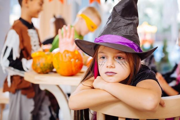 Garota cansada. linda garota com longos cabelos escuros usando uma fantasia de feiticeiro de halloween e se sentindo cansada durante a festa