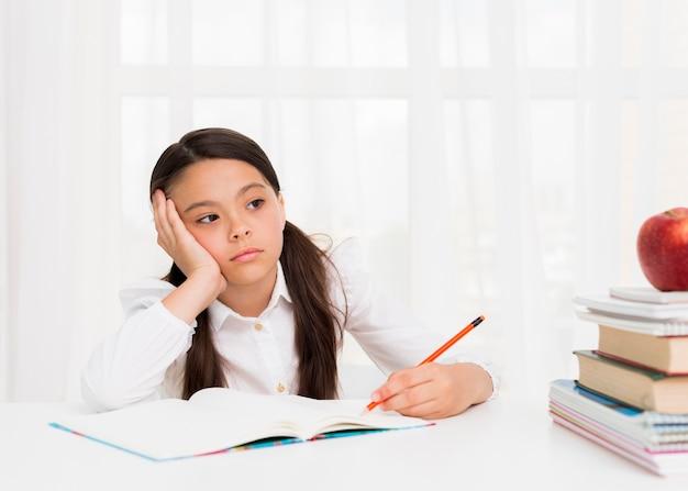 Garota cansada, pensando e fazendo lição de casa