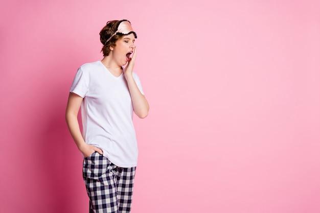 Garota cansada segurando a mão perto de bocejo aberto em fundo rosa