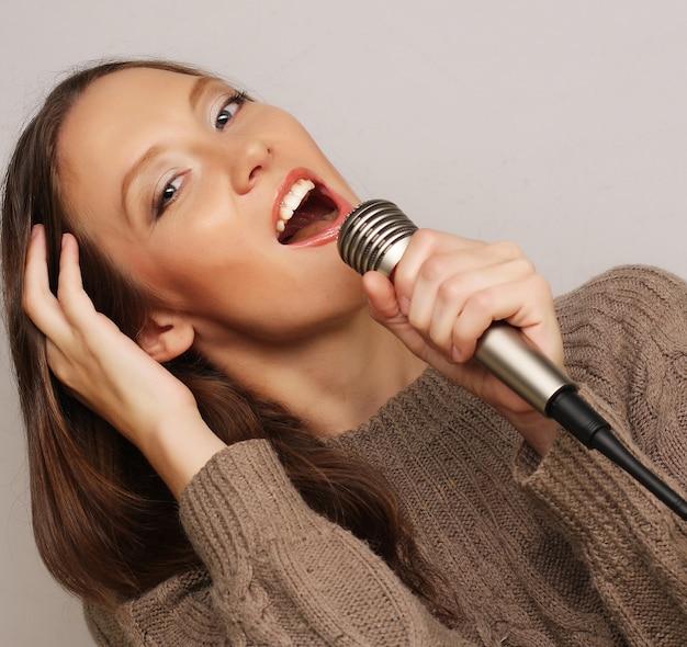 Garota cantora feliz. mulher de beleza com microfone sobre fundo branco.