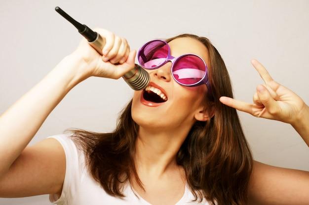 Garota cantora feliz. mulher de beleza vestindo camiseta branca e grandes óculos de sol com microfone sobre fundo branco. estilo ipster