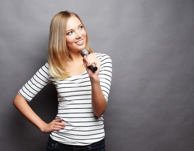 Garota cantora feliz. mulher de beleza vestindo camiseta com microfone sobre o espaço cinza.