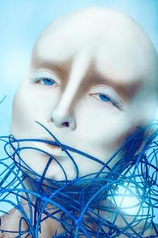 Garota careca com arte corporal em superfície azul