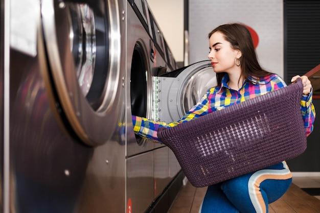 Garota carrega roupa em uma máquina de lavar. mulher na lavanderia pública