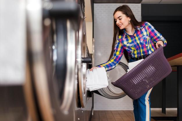 Garota carrega roupa em uma máquina de lavar. mulher na lavanderia
