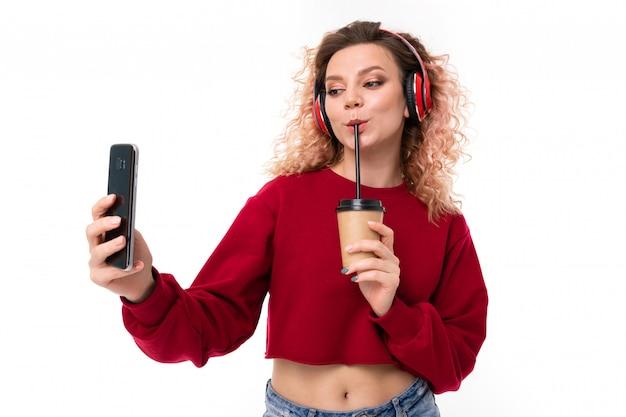 Garota caucasiana com cabelo loiro encaracolado bebe café e conversando com amigos, retrato isolado