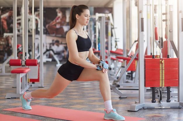Garota caucasiana de aptidão fazendo exercícios de alongamento no chão no ginásio. foto de comprimento total de jovem no centro de fitness. atlética feminina relaxante após o treino. conceito de alongamento, esporte e motivação.