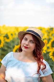 Garota caucasiana de cabelos vermelhos jovens no verão algodão vestido e chapéu de palha em um campo de girassóis amarelos em um dia ensolarado.
