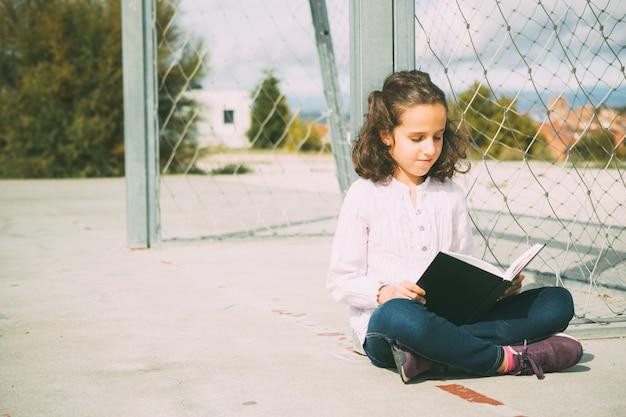 Garota caucasiana de frente com cabelo castanho sentada no chão enquanto lê um livro na rua