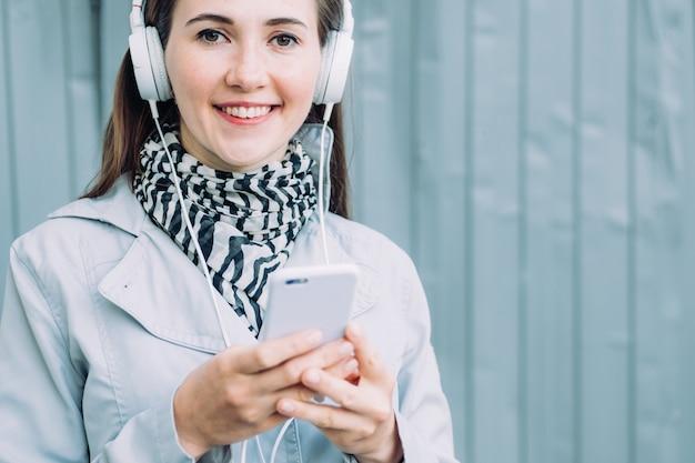 Garota caucasiana em fones de ouvido, sorrindo e olhando para a câmera enquanto ouve música