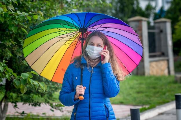 Garota caucasiana em uma máscara protetora fica em uma rua vazia em uma parada de ônibus sob um guarda-chuva na chuva de primavera e fala ao telefone.