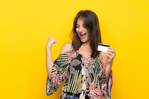 Garota caucasiana em vestido colorido isolado parede amarela segurando um cartão de crédito