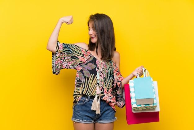 Garota caucasiana em vestido colorido isolado parede amarela segurando um monte de sacolas de compras