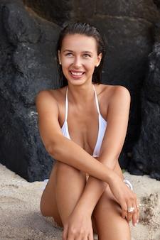 Garota caucasiana feliz gosta de verão ao ar livre, molha o corpo perfeito