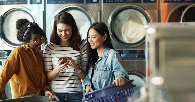 Garota caucasiana, mostrando fotos em smartphone para amigas de raças mistas enquanto máquinas de lavar roupa, trabalhando e limpando roupas. mulheres multiétnicas que olham o vídeo no telefone no serviço de lavanderia.