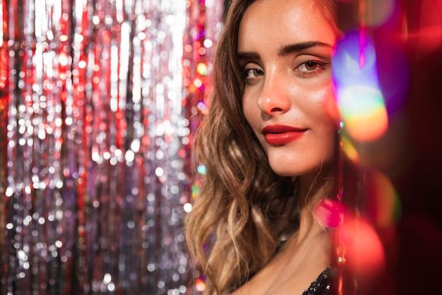 Garota cercada por cortinas borradas de brilhos