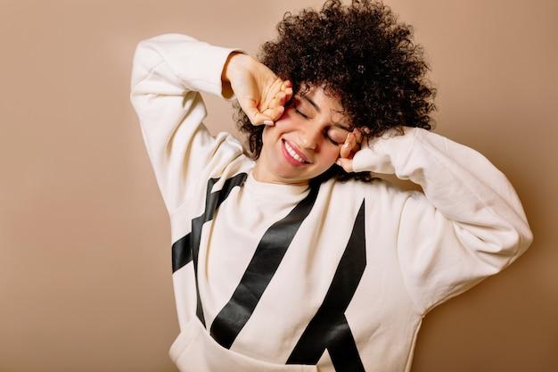 Garota charmosa e descontraída com cachos e blusa branca, sorrindo com os olhos fechados e se espreguiçando sobre uma parede isolada