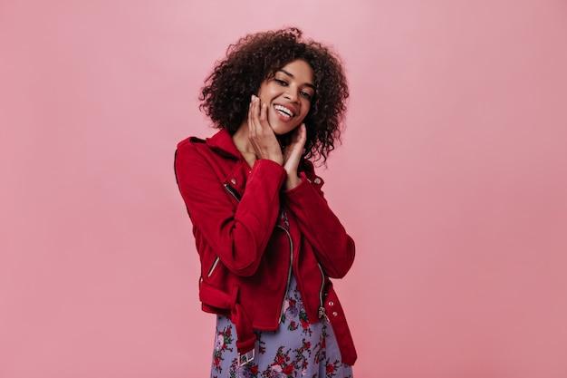 Garota charmosa em uma jaqueta vermelha rindo na parede rosa