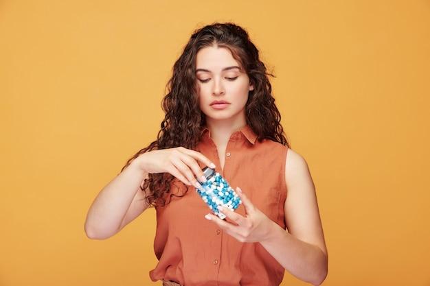 Garota chateada com cabelo encaracolado em pé com os braços cruzados enquanto mede a temperatura corporal