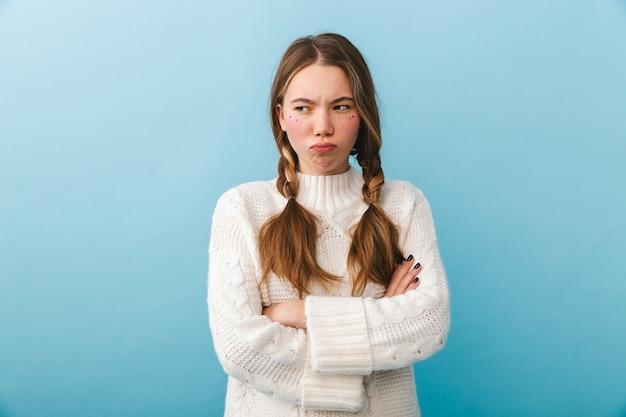 Garota chateada com suéter isolada, braços cruzados