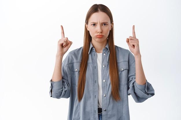 Garota chateada ou com raiva franzindo a testa, emburrada e apontando o dedo para algo ruim, sendo ciumenta, quer algo, reclamando, decepcionada contra uma parede branca