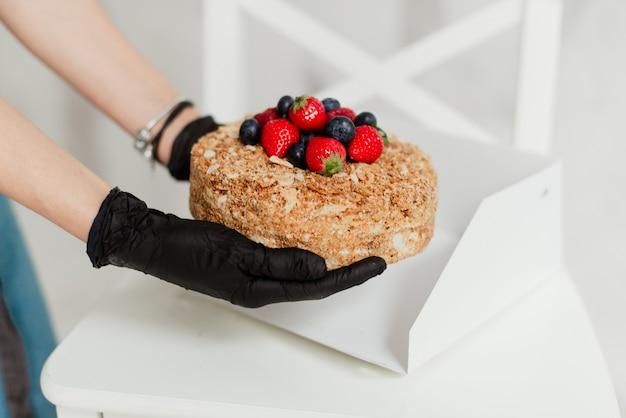 Garota chef de confeitaria com luvas pretas segurando uma comida deliciosa de bolo de mel