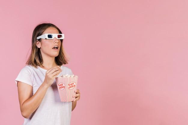 Garota chocada com pipoca e óculos 3d