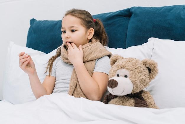 Garota chocada, sofrendo de frio e febre olhando para termômetro