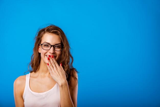 Garota cobre a boca com a mão e ri.