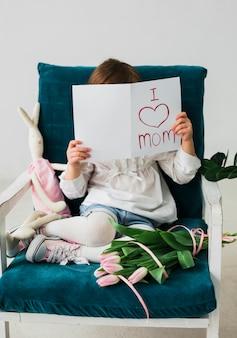 Garota cobrindo o rosto com cartão com eu amo a inscrição de mãe